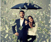 Paar unter Regenschirm im Geldregen